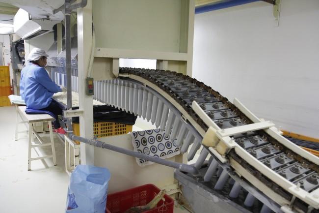 콘돔 공장 근로자가 불량 콘돔을 찾기 위해 금속봉에 콘돔을 끼우고 있다. 전기가 흐르는 액체를 지날 때 콘돔을 끼운 금속봉에 전기가 통하면 해당 콘돔은 불량이다. - 증평=우아영 기자 wooyoo@donga.com 제공